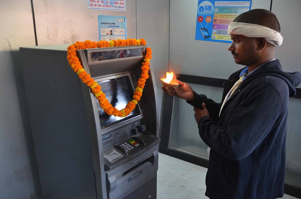 A man offering puja to an ATM machine in Mirzapur. Photo: UNI