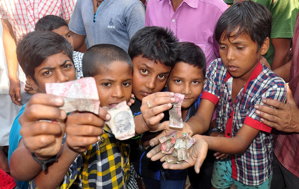 Children showing torn notes of Rs 500 and Rs 1,000 found near a drain in Guwahati. Photo; UNI