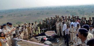 Police officers and Special Task Force soldiers stand beside dead bodies of the suspected members of the banned Students Islamic Movement of India (SIMI), who escaped the high security jail in Bhopal, and later got killed in an encounter on the outskirts of Bhopal, India. Photo: UNI