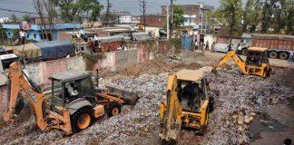 JCB machines crushing the bottles of country made liquor at Danapur in Patna. Photo: UNI