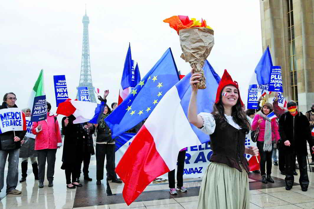 """People celebrated Macron's win with French and European flags and with placards that read: """"France tells Hate: Never Again"""". Photo: UNI"""