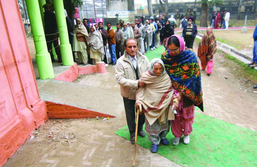 An old lady gets help to cast her vote as other voters queue up. Photo: UNI