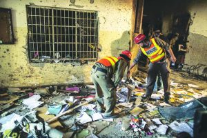 A rescue team goes through the debris inside Army Public School in Peshawar after a terrorist attack. Photo: UNI