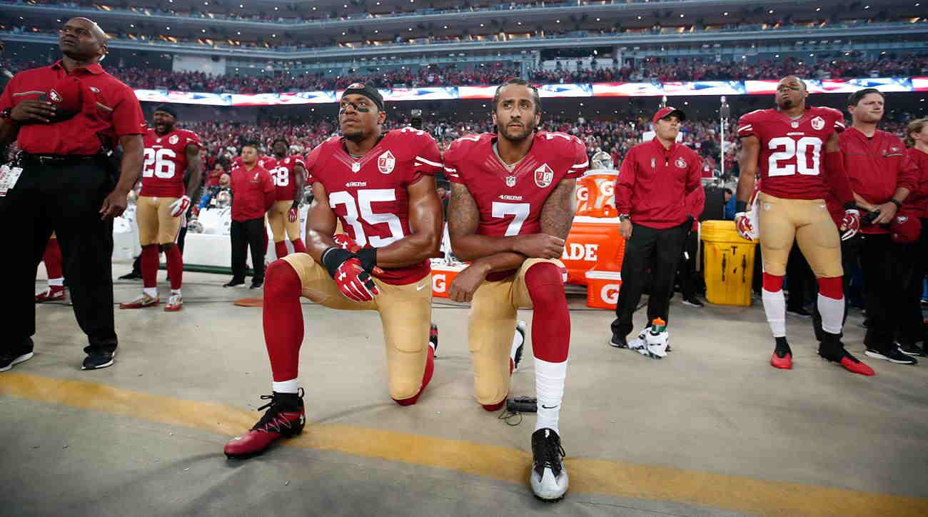 Football player Colin Kaepernick (without cap) kneeling during the anthem to protest the shooting of African-Americans by police officers