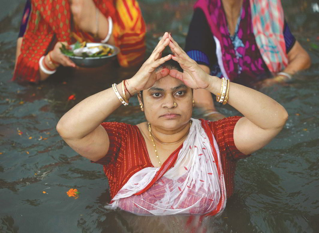 A Hindu woman takes a Mahashtami dip in the Brahmaputra. Bangladeshi Hindus share roots and customs with their Indian counterparts. Photo: UNI