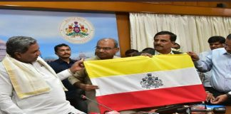 Siddaramaiah along with other officials unveiling the karnataka state flag
