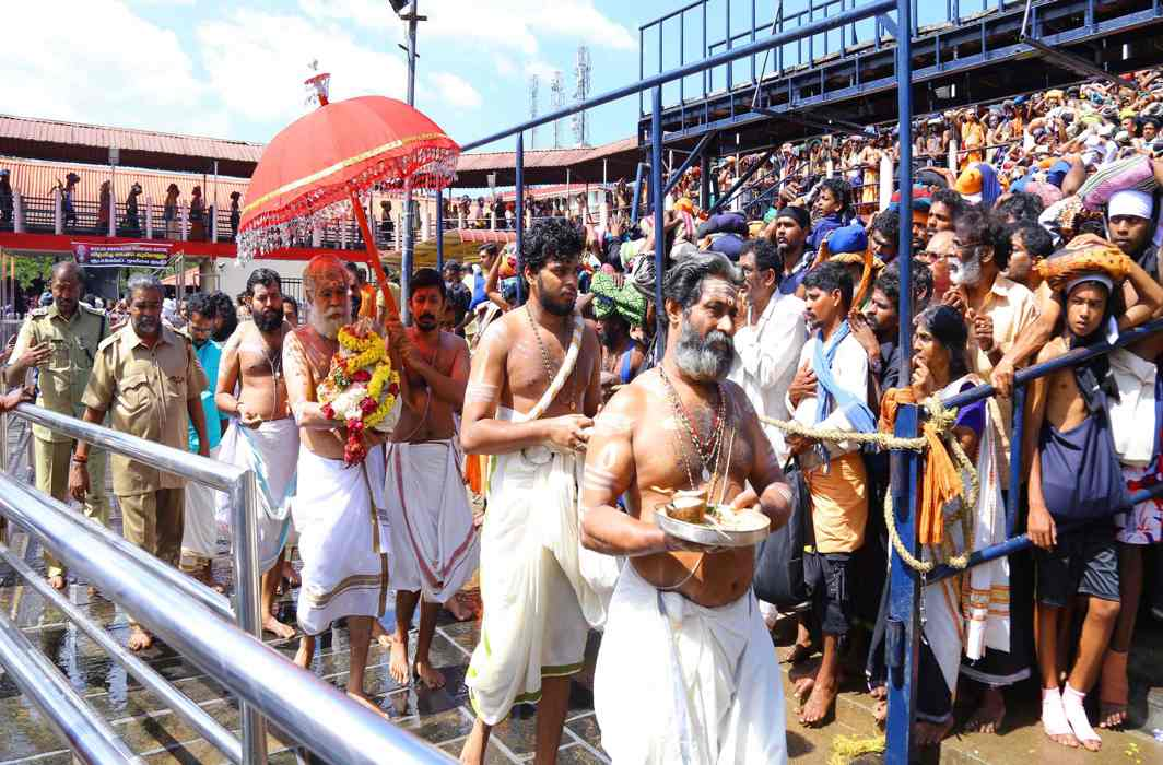 Thousands of devotees witness the installation ceremony of the new gold-plated flag mast at the Ayyappa temple in Sabarimala