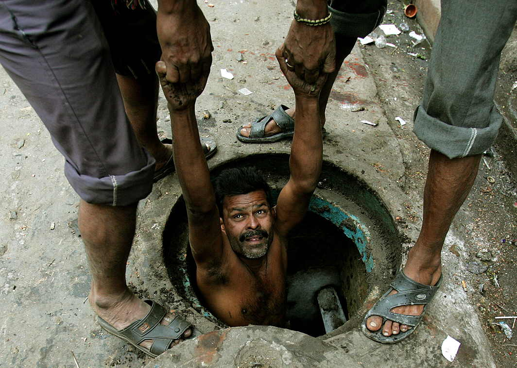 Third pic: A labourer is lowered to clean a sewage line in Kolkata