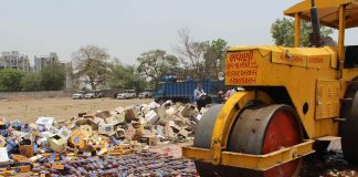 Police officials destroy seized illegal liquor stock in Ahmedabad/Photo: UNI