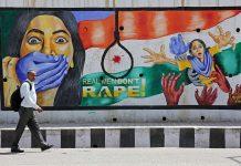 A man walks past graffiti depicting a message against rape of minors/Photo: UNI