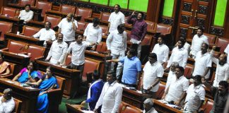 Congress MLAs stand up his chair during the assembly session at Vidhana Soudha in Bengaluru on July 19/Photo: UNI