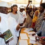 Gambian President Yahya Jammeh holds a copy of the Quran while speaking to a poll worker at a polling station during the presidential election in Banjul, Gambia, December 1, 2016, Reuters/UNI