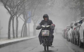 THROUGH THE HAZE: A man rides an electric bicycle during a snowfall in Beijing, Reuters/UNI