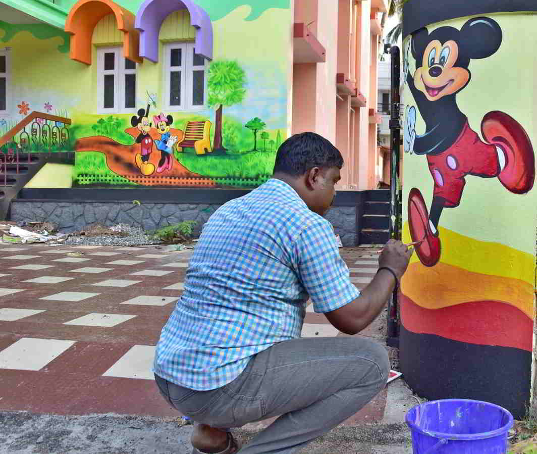 BRIGHTER, MERRIER: An artist gives finishing touches to his work on the walls of a nursery school in Thiruvananthapuram, UNI