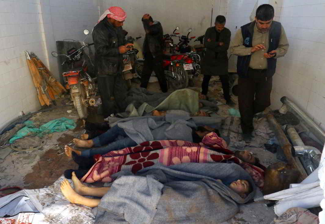 DASTARDLY ACT: Men gather near bodies, after a suspected gas attack in the town of Khan Sheikhoun in rebel-held Idlib, Syria, by government forces