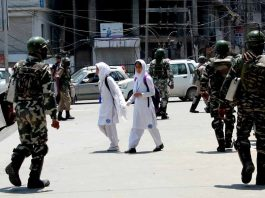 IN SHOCK: College students pass by the security forces to their homes after classes were suspended in educational institutions as a precautionary measure following the killing of Hizbul Mujahideen commander Sabzar Bhat in an encounter in Pulwama, UNI