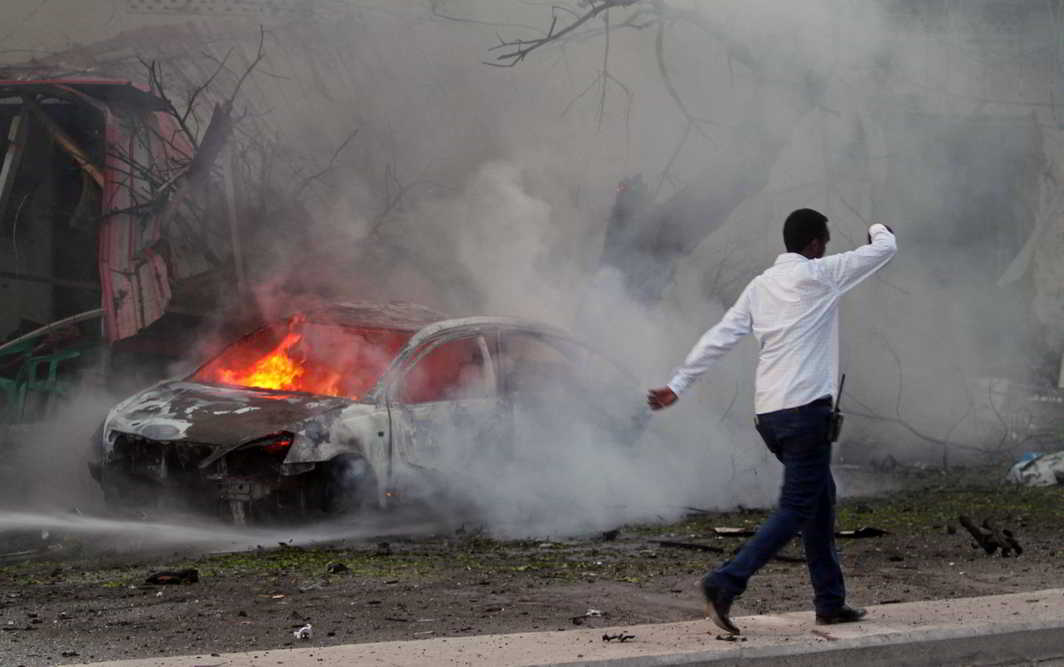 SUICIDE STRIKE: A Somali man walks past the wreckage of a burning vehicle at the scene of an attack where a car laden with explosives rammed into a cafeteria in capital Mogadishu, Reuters/UNI