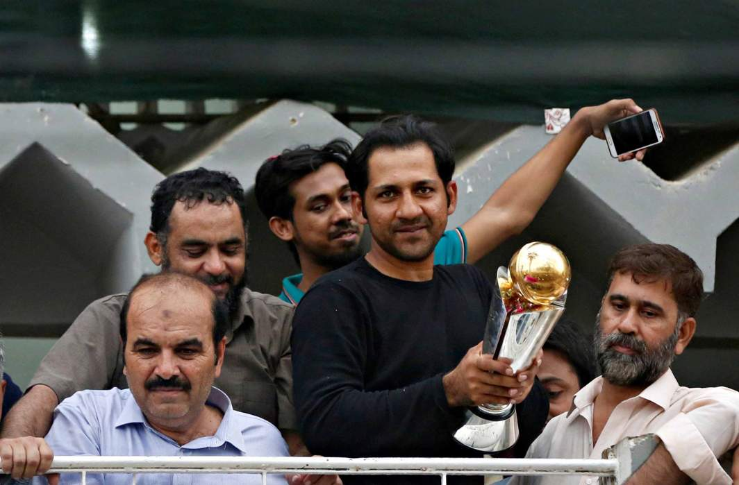 HERO'S WELCOME: Pakistan's Sarfraz Ahmed stands with friends and family members as he celebrates winning the ICC Champions Trophy upon his arrival at his house in Karachi, Pakistan, Reuters/UNI