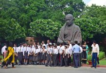 YOUNG MINDS: School students visiting Parliament house pose for a photograph in front of the Gandhi statue, in New Delhi, UNI