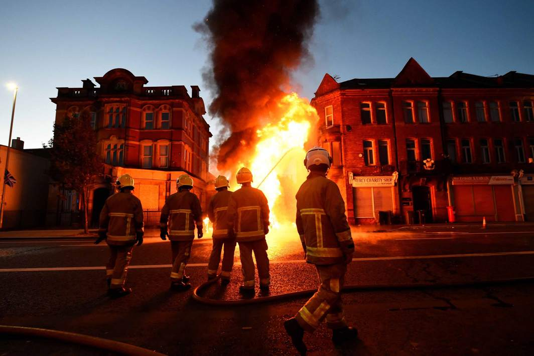 OUT OF HAND: Firefighters tackle a bonfire in East Belfast before the Twelfth of July celebrations held by members of Loyalist Orders in Belfast, Northern Ireland, Reuters/UNI
