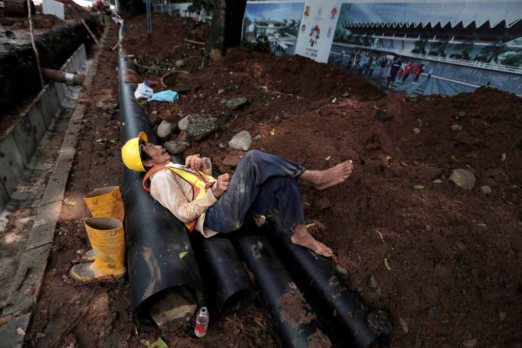 FORTY WINKS: A worker takes a nap on top of pipes at the renovation site of the Gelora Bung Karno Sport Complex in Jakarta, Indonesia, Reuters/UNI
