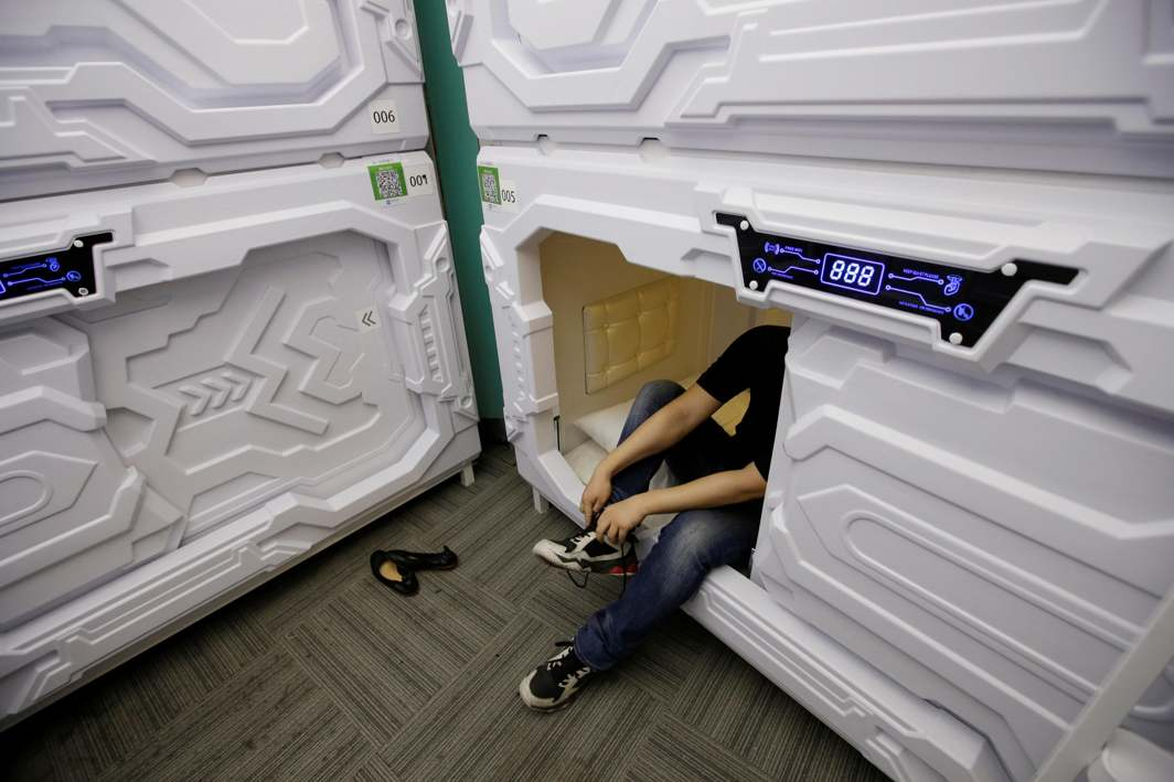 SLEEP TIGHT: An IT employee takes off shoes as he prepares to sleep in a capsule bed unit at Xiangshui Space during lunch break in Beijing's Zhongguancun area, China, Reuters/UNI