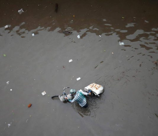 NATURE THE TEACHER: A man pushes his bicycle through a water-logged street after heavy rains in Ahmedabad, Reuters/UNI