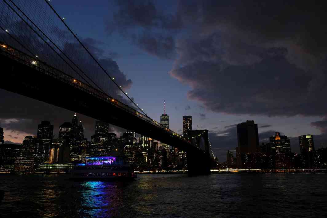 DARK NIGHT RISES: A ferryboat passes under Brooklyn Bridge in front of the night skyline of Lower Manhattan in New York City, US, at dusk, Reuters/UNI