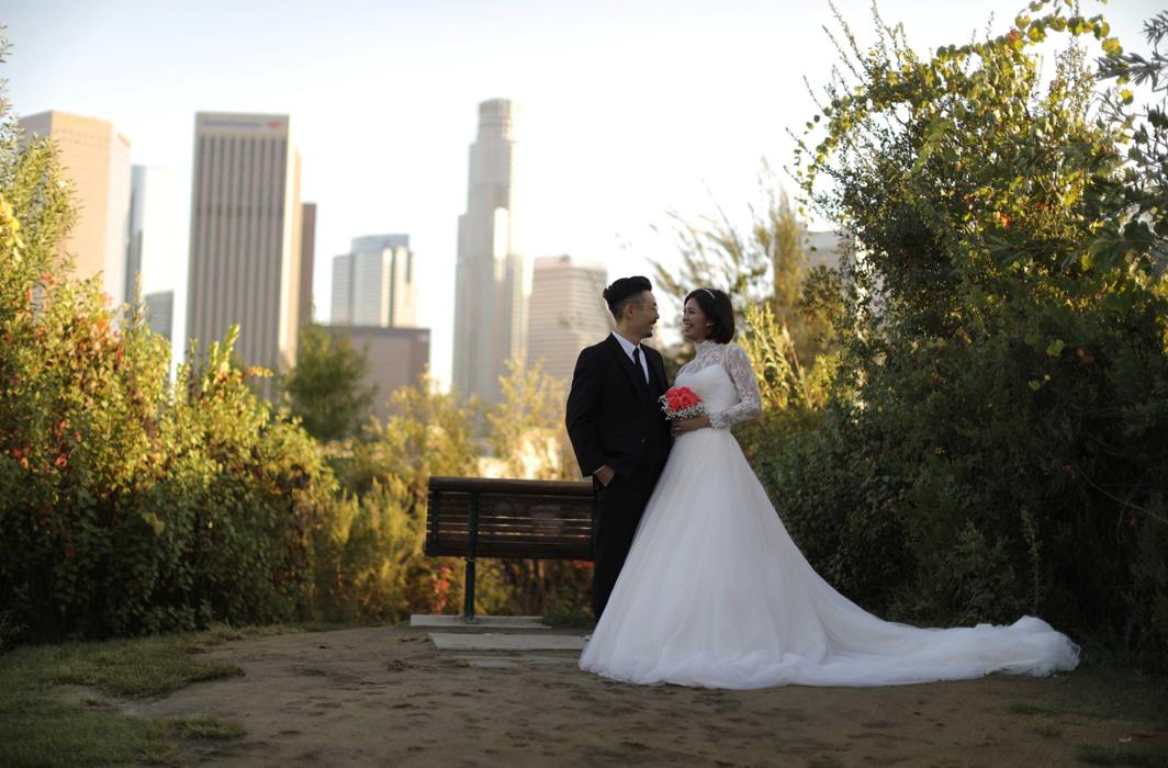 JUST MARRIED: A couple poses for a photo in front of the downtown Los Angeles skyline, California, US, Reuters/UNI