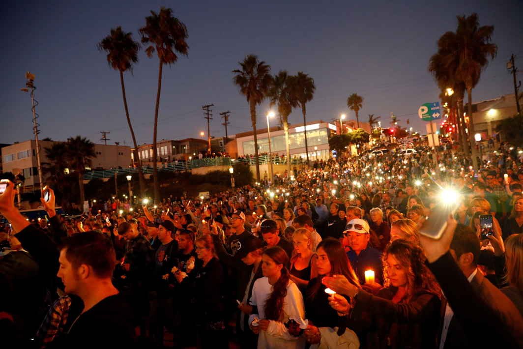 IN DEFIANCE: People hold candles and flashlights into the air during a memorial for Rachael Parker and Sandy Casey, Manhattan Beach city employees and victims of the October 1st Las Vegas Route 91 music festival mass shooting, in Manhattan Beach, California, Reuters/UNI