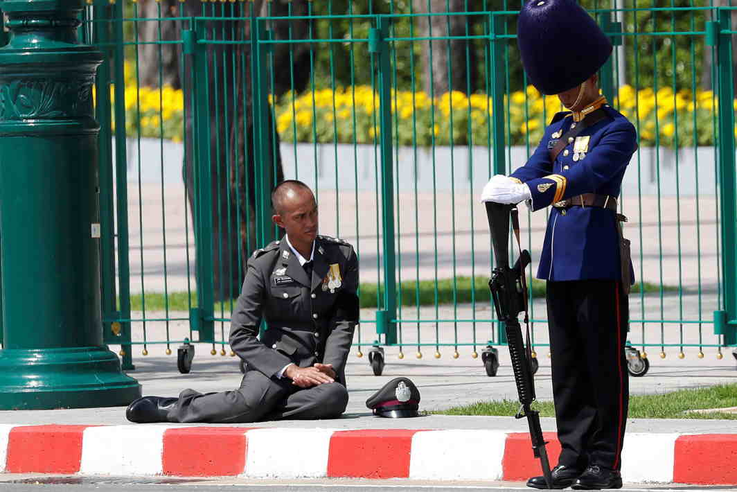 BOW TO STATURE: A royal guard and a policeman show their respect during a procession to transfer the royal relics and ashes of Thailand's late King Bhumibol Adulyadej from the crematorium to the Grand Palace in Bangkok, Thailand, Reuters/UNI