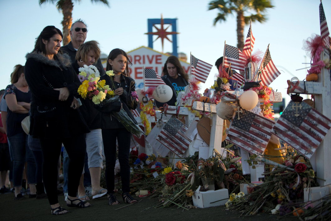 "INDELIBLE TRAUMA: Samantha Langton, 10, (C) places flowers at 58 wood crosses, with the names and photos of the October 1 mass shooting victims, in the median of Las Vegas Boulevard South near the ""Welcome to Las Vegas"" sign in Las Vegas, Nevada, US, Reuters/UNI"