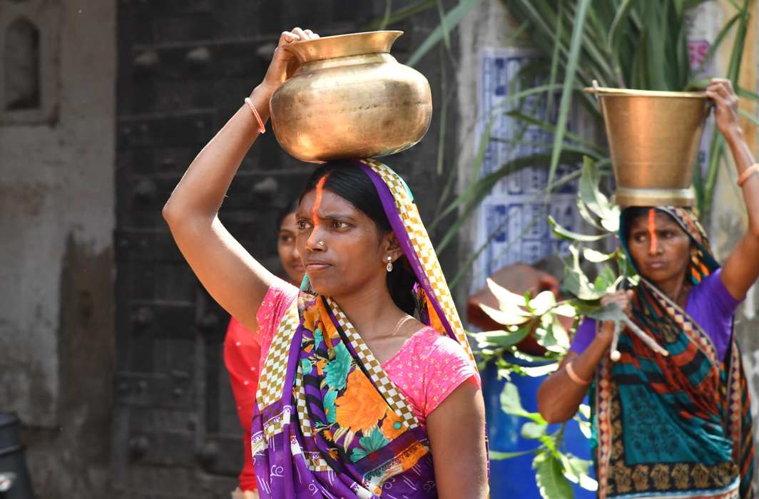 WALK OF FAITH: Women devotees carry pots filled with holy water of Falgu river for preparing prasad on the occasion of Chhatth Puja festival in Bodhgaya, UNI