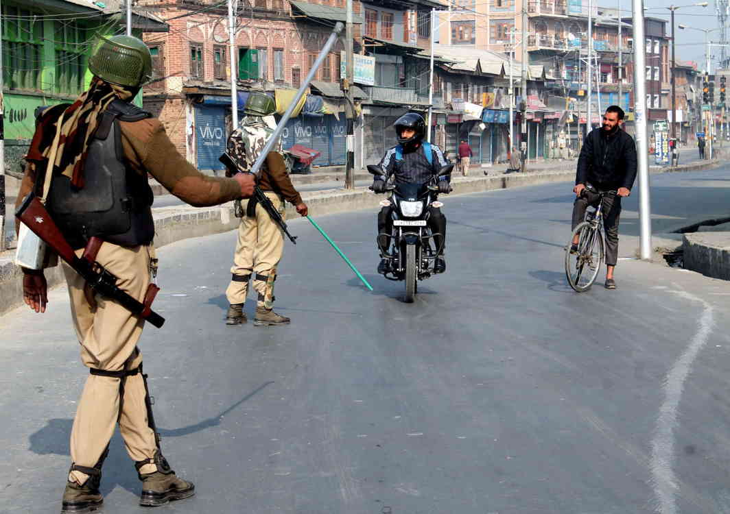 THIS WAY: Security personnel direct commuters to take another route at Gojiwara amid curfew-like restrictions imposed by the authorities in downtown and Shehar-e-Khas besides parts of the civil lines in Srinagar to prevent any violence following a general strike call issued by separatists in Kashmir valley, UNI