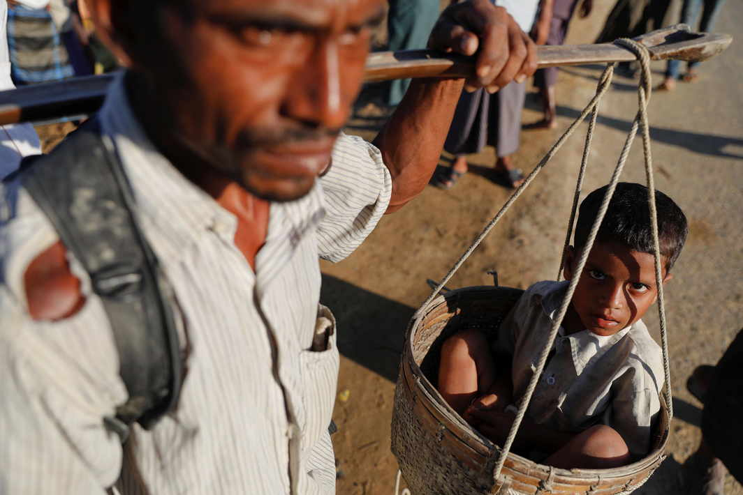 WALK ON: A Rohingya man carries his daughter in a basket along a road between refugee camps near Cox's Bazar, Bangladesh. He carried both his young daughters for eight days as he escaped attackers in Myanmar, Reuters/UNI