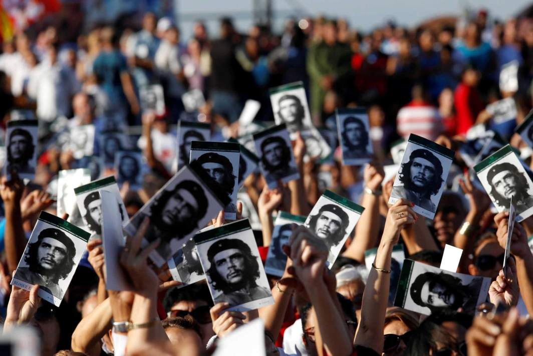 "REMEMBER: People hold images of late Cuban revolutionary hero Ernesto ""Che"" Guevara during a ceremony commemorating the 50th anniversary of his death, Santa Clara, Cuba, Reuters/UNI"