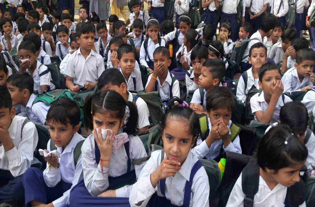 CAN'T BREATHE: Schoolchildren cover their faces to protect themselves from gas leaked out of a sugar factory in Shamli, Uttar Pradesh. About 200 were affected, UNI