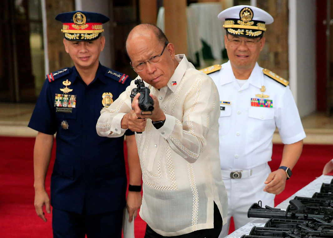 GUN FOR A GIFT: Defence secretary Delfin Lorenzana (C) aims an automatic rifle during the turnover ceremony of China's urgent military assistance to the Philippines at the military camp in Camp Aguinaldo in Quezon City, Manila, Philippines, Reuters, UNI