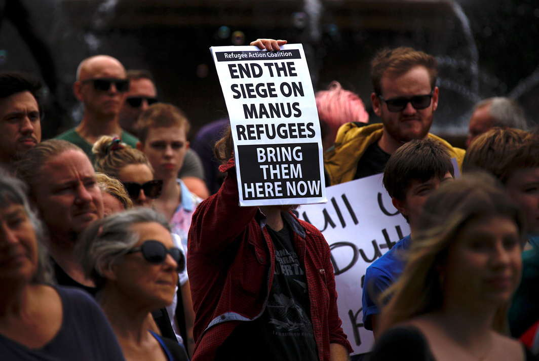 HOME AWAY FROM HOME: Refugee advocates hold placards as they participate in a protest in Sydney, Australia, against the treatment of asylum-seekers at Australia-run detention centres located at Nauru and Manus Island, Reuters/UNI