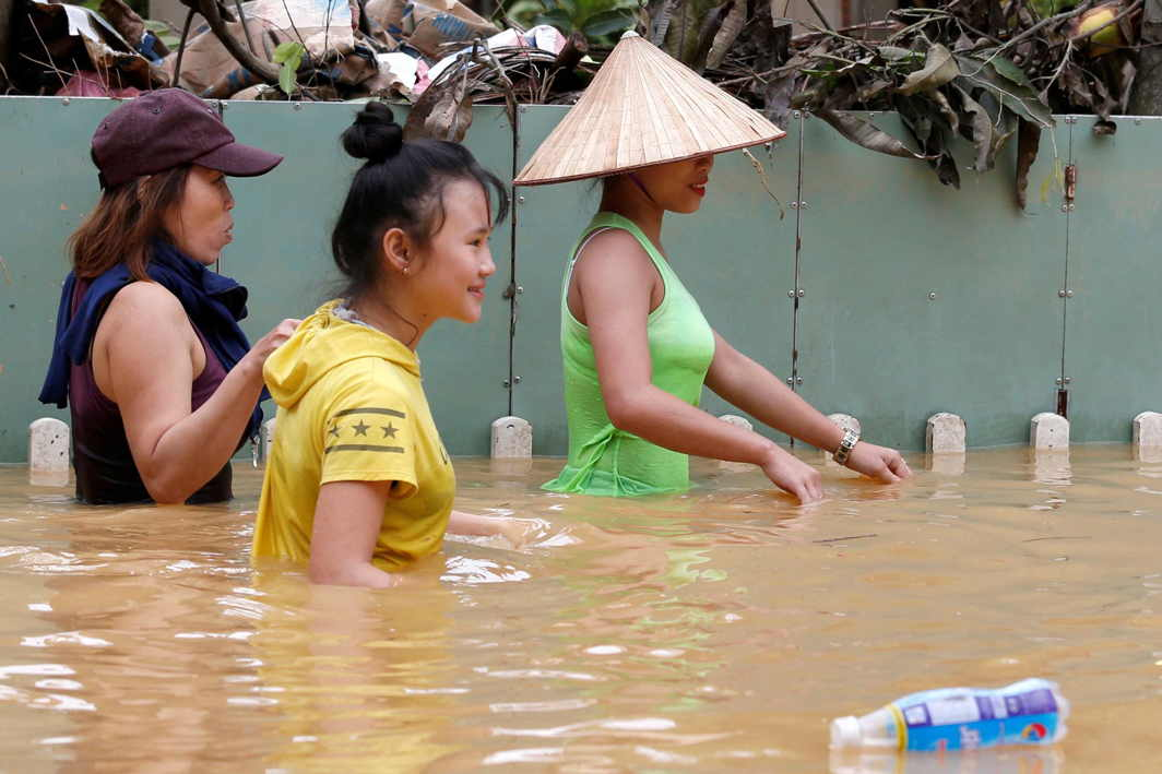 IN GOOD SPIRITS STILL: Women wade through floodwaters brought by Typhoon Damrey in the ancient UNESCO heritage town of Hoi An, Vietnam, Reuters/UNI