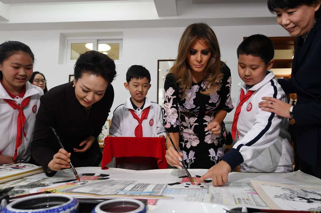 PLAYING WITH COLOURS: US First Lady Melania Trump (C) and China's First Lady Peng Liyuan (2nd L) paint the eyes of panda figures in a calligraphy class during a visit to Banchang Primary School in Beijing, Reuters/UNI