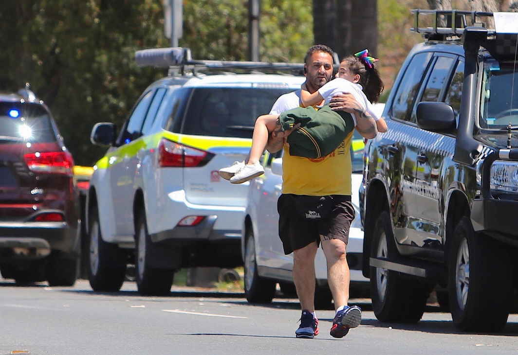 HELPING HANDS: A man carries a child near where a vehicle crashed into a primary school classroom in the Sydney suburb of Greenacre in Australia, Paul Braven/AAP/Reuters/UNI