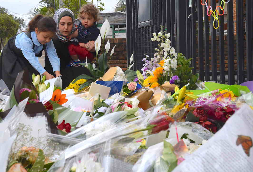 SENSELESS TRAGEDY: A mother and her young children place flowers outside the gates of the Banksia Road Public School, the day after a vehicle crashed into one of the primary school's classroom killing two children, in the Sydney suburb of Greenacre in Australia, Reuters/UNI