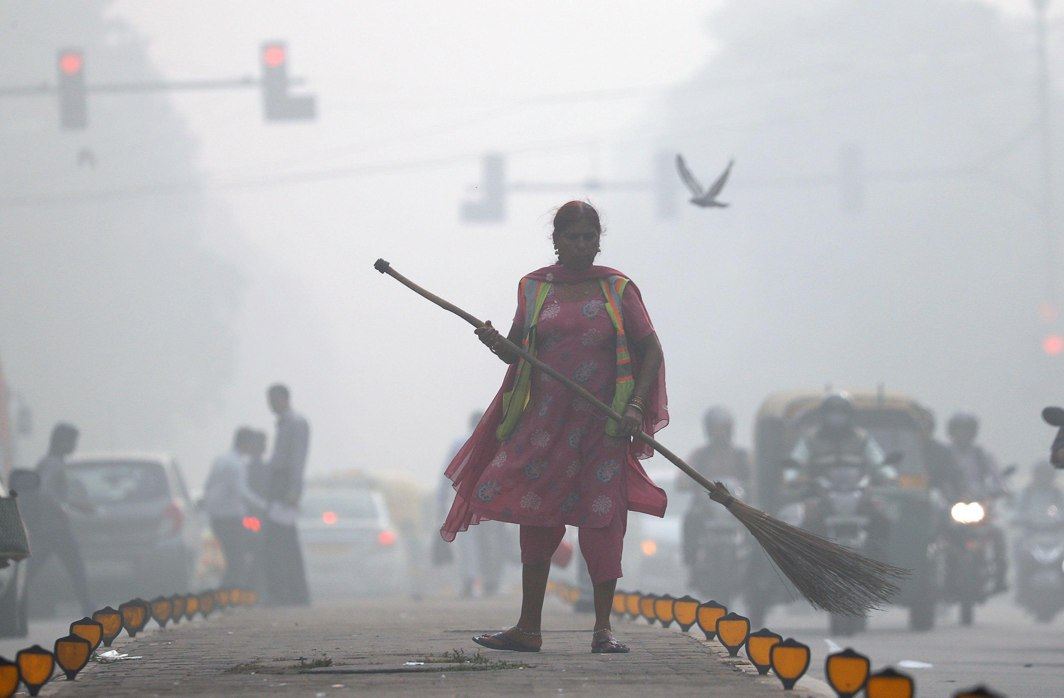JUST AN ORDINARY DAY: A street cleaner works in heavy smog in Delhi, India, Reuters/UNI