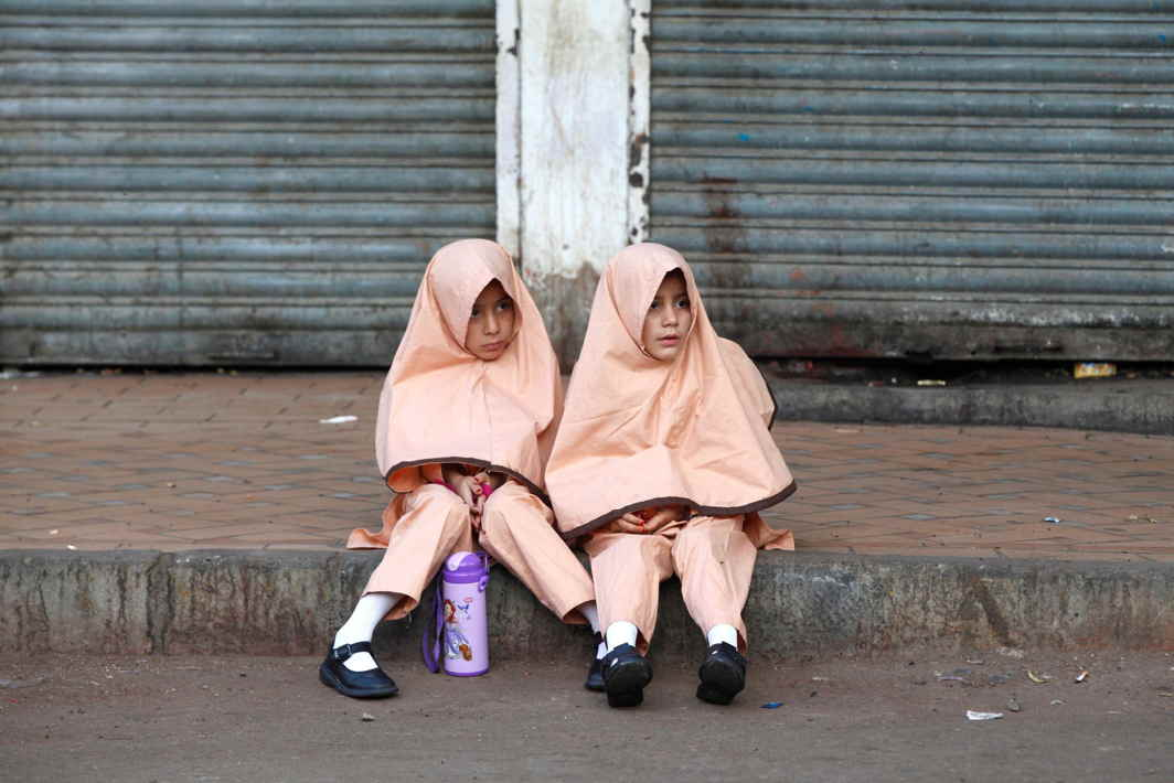 LIMITED CHOICES: Girls in uniform sit along a sidewalk while waiting for school van in Karachi, Pakistan, Reuters/UNI