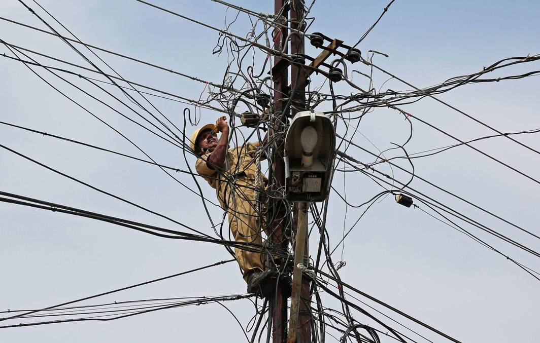 DANGEROUS TANGLE: A worker repairs power lines on a pole in Kochi, India, Reuters/UNI