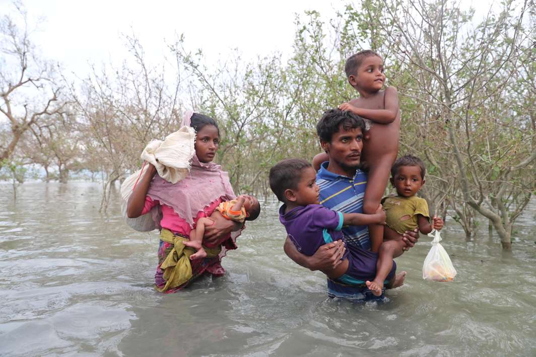 NEVER GIVE UP: Rohingya refugees walk on the water after crossing the Naf river with an improvised raft to reach Bangladesh in Teknaf, Bangladesh, Reuters/UNI