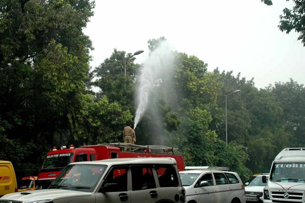 FIGHTING POLLUTION: Delhi Fire Services personnel sprinkle water on trees to settle the dust near India Gate, UNI
