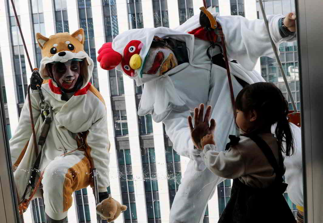 FRIENDS AT MY WINDOW: A girl looks at window cleaners, dressed as a rooster, this year's Chinese zodiac animal, and a dog, next year's Chinese zodiac animal, while they clean the windows of Ryumeikan hotel during a promotional event to celebrate the upcoming new year in Tokyo, Japan, Reuters/UNI