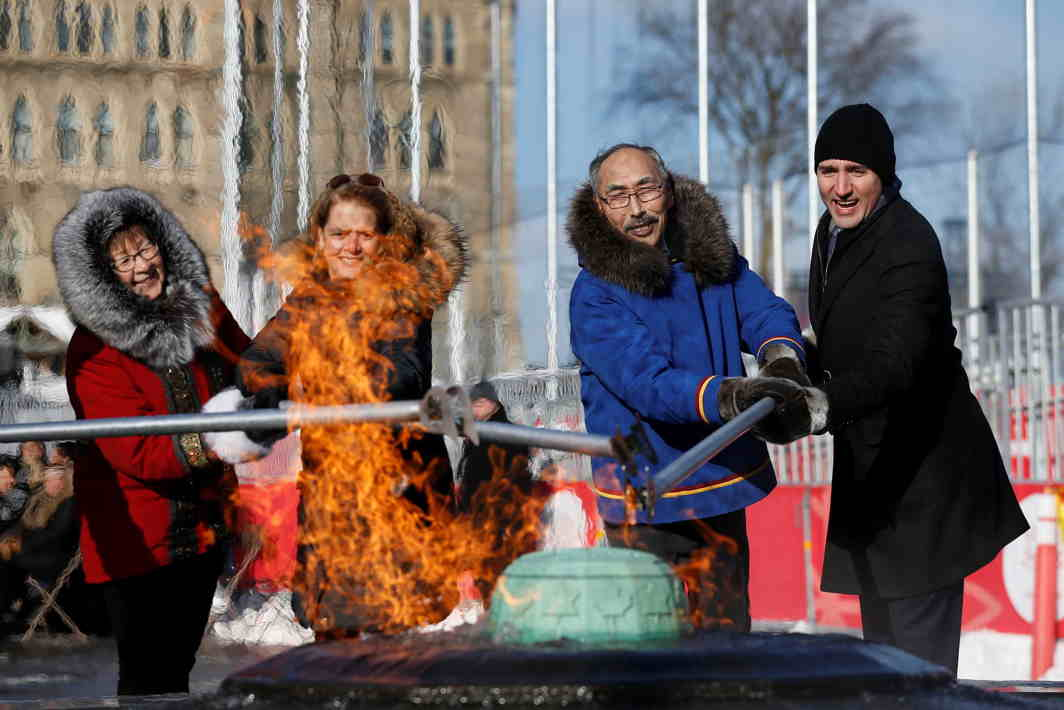 STAND TOGETHER: Canada's Prime Minister Justin Trudeau (right) helps light the Centennial Flame with Nunavut's Premier Paul Quassa (second right), Governor General Julie Payette (second left) and Nunavut's Commissioner Nellie Kusugak, during a ceremony on Parliament Hill in Ottawa, Ontario, Canada, Reuters/UNI